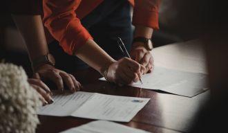 deux personnes consultant des documents, dont une qui signe