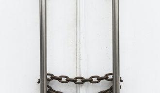 des poignées d'une porte fermées par une chaîne et un cadenas