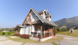 une maison blanche, grise et marron sous un ciel bleu