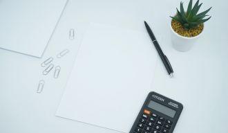une calculatrice, un stylo, des feuilles et une plante sur une table