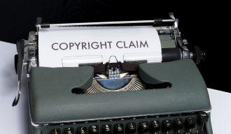 """une machine à écrire de laquelle sort une feuille de papier où l'on voit écrit """"copyright claim"""""""
