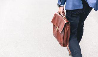 une personne en costume avec un porte-documents en train de marcher