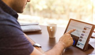 un homme regardant un site internet sur sa tablette