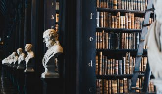une bibliothèque avec des statues de bustes